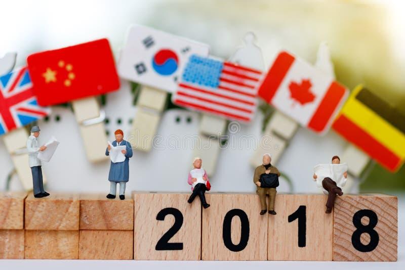 Miniatur ludzie: Biznesu drużynowy czytanie na drewnianym bloku z liczbą 2018 obrazy stock