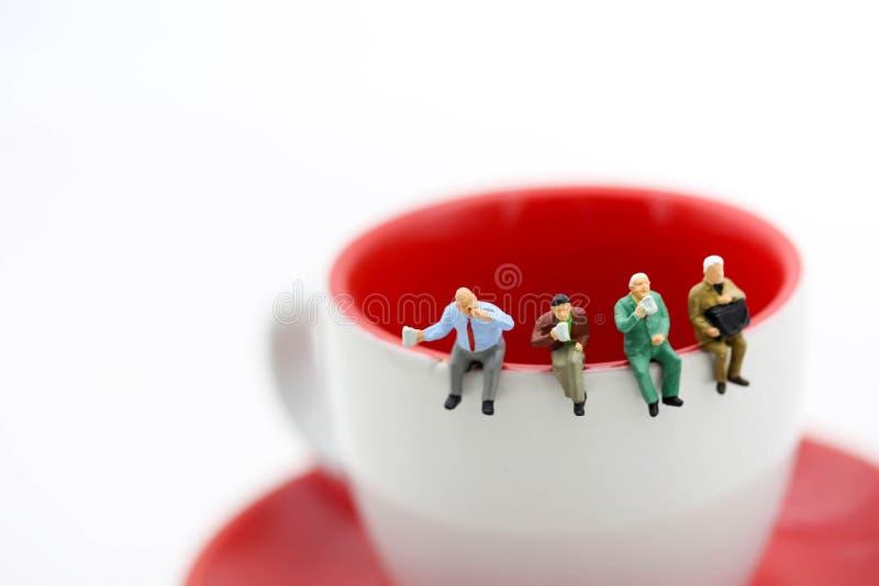 Miniatur ludzie: siedzieć na filiżance kawy używać jako backgrou fotografia royalty free