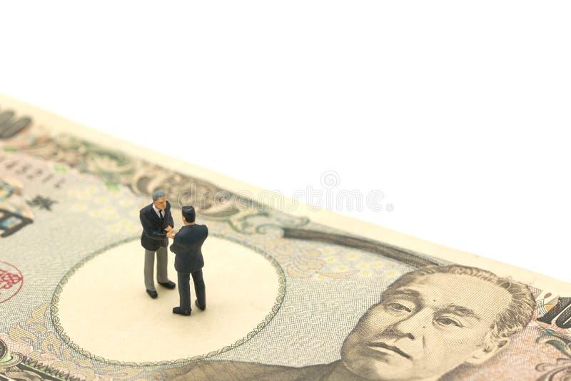 Miniatur2 menschen, die Geschäftsmänner Hände rütteln, stehen auf japanischen Banknoten wert 10.000 Yen unter Verwendung als Hint stockfotos