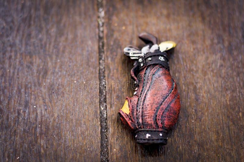 Miniatura ajustada do golfe no fundo de madeira foto de stock