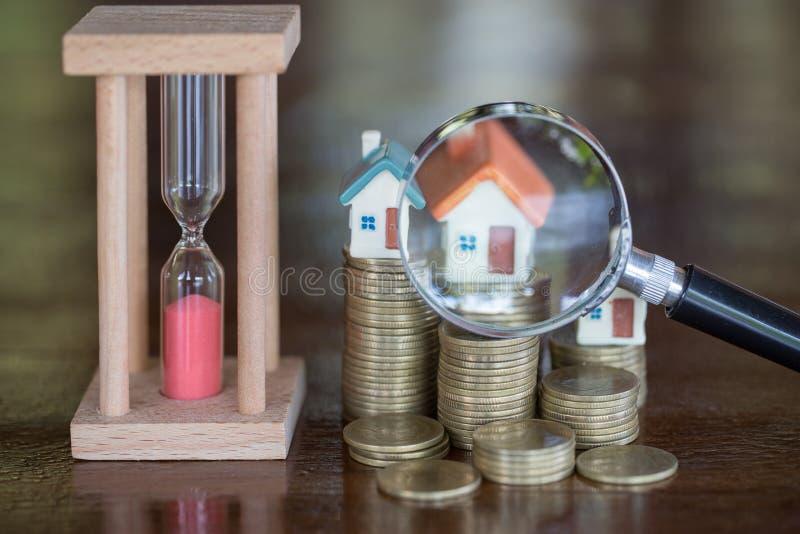 Miniatura da casa com lupa e moeda, escolha de lugar para a constru??o, da hipoteca, alojamento alugado, casa foto de stock