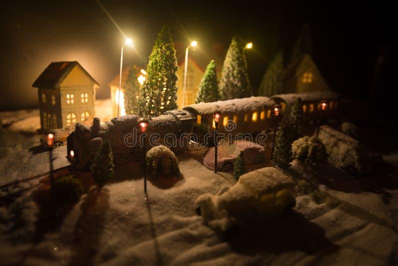 Miniatura da cena com casas do Natal, estação de caminhos de ferro do inverno, árvores, cobertas na neve Cena das noites Ano novo foto de stock