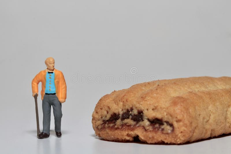 Miniatura de un viejo hombre y de una galleta imágenes de archivo libres de regalías