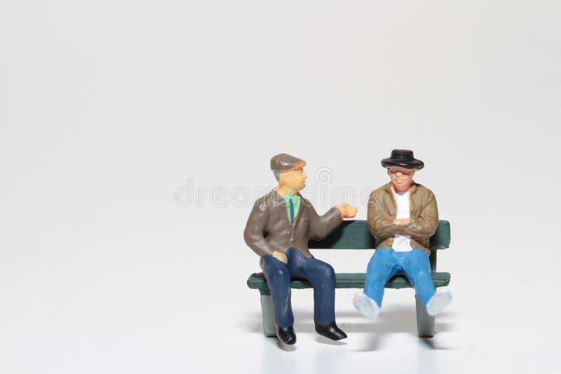 Miniatura di un uomo anziano che parla su un banco fotografie stock