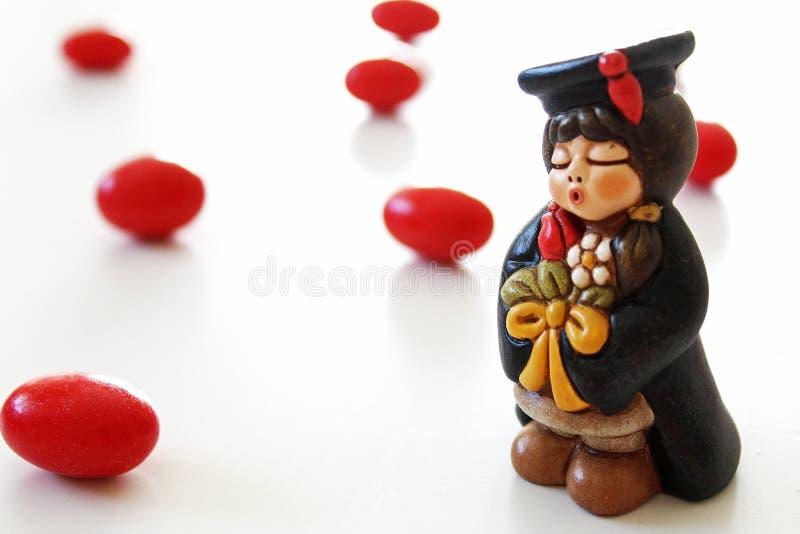 Miniatura do estudante da graduação no fundo branco, doces vermelhos imagens de stock