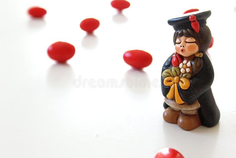 Miniatura do estudante da graduação no fundo branco e em doces vermelhos foto de stock