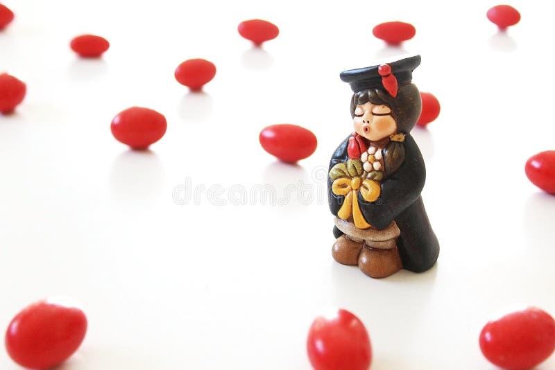 Miniatura do estudante da graduação no fundo branco e em doces vermelhos imagens de stock royalty free