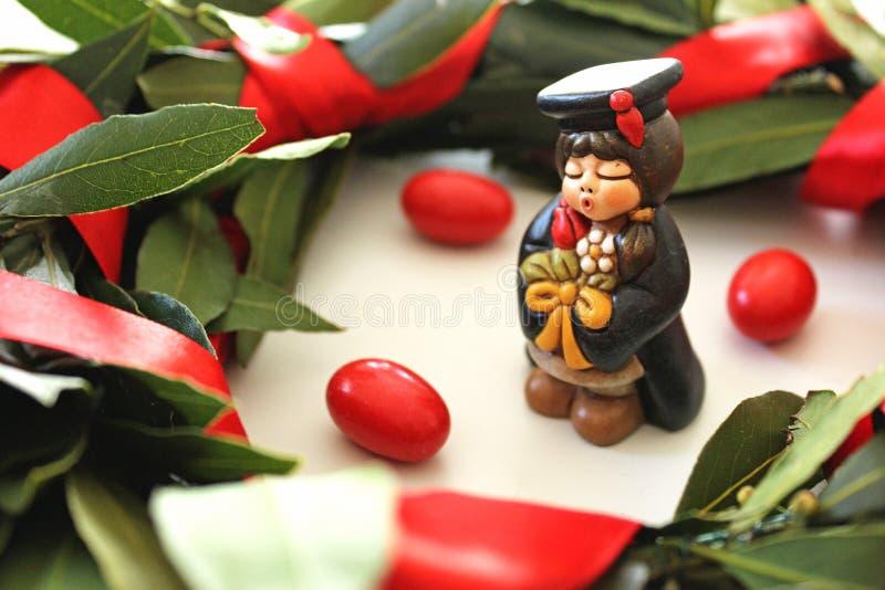 Miniatura do estudante da graduação no fundo branco, na coroa verde do louro e em doces vermelhos imagem de stock royalty free
