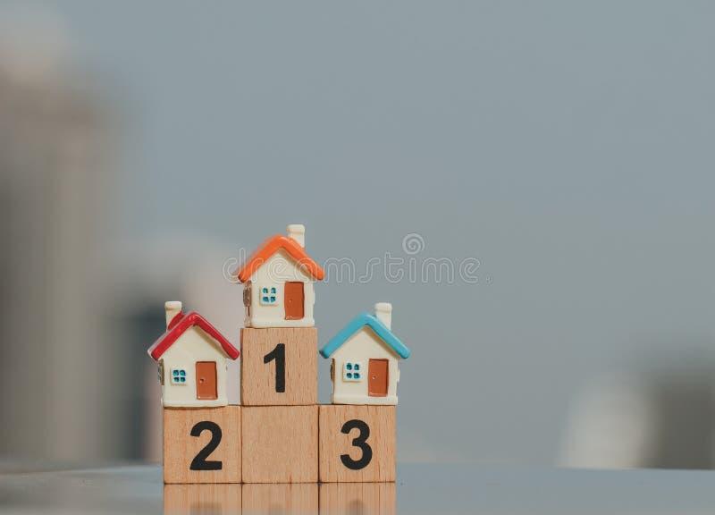 Miniatura domy na drewnianej blokowej liczbie jeden dwa trzy u?ywa? jako biznesowy i maj?tkowy poj?cie zdjęcia stock