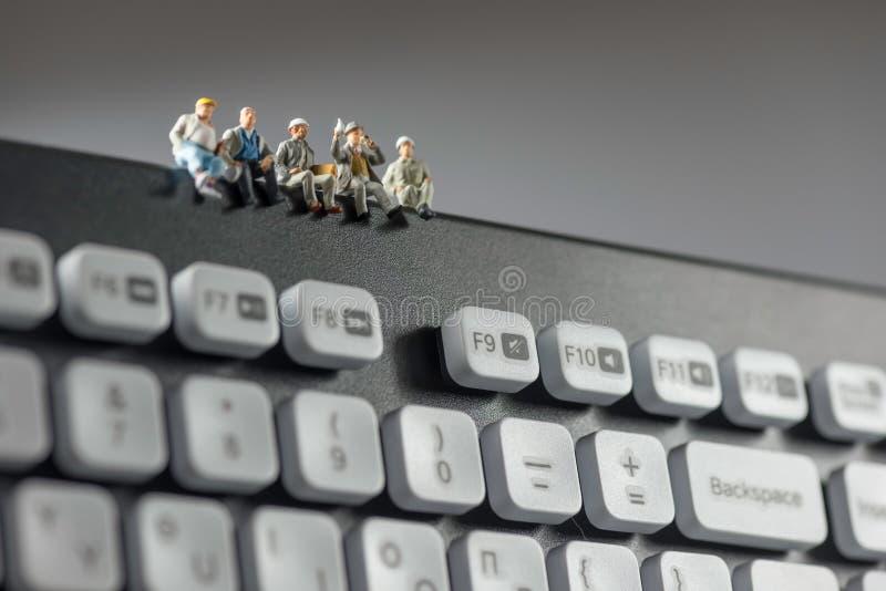 Miniaturarbeitskräfte, die auf Tastatur sitzen Getrennt auf Weiß lizenzfreie stockfotos