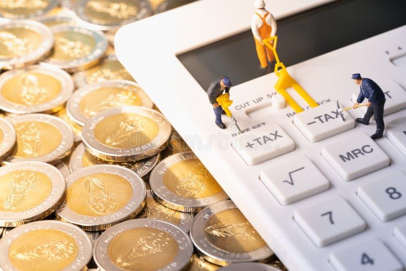 Miniaturarbeitskräfte, die Steuerknopf auf Taschenrechner auf Stapel von Münzen graben stockbild