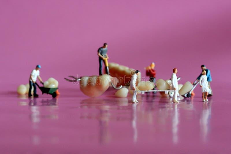 Miniaturarbeitskräfte, die zahnmedizinische Verfahren durchführen Zahnmedizinisches Büro AR stockbild