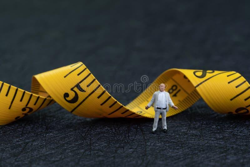 Miniaturdicker mann mit Bauchstellung mit gelbem messendem Band auf dunklem schwarzem Hintergrund mit als Anfangsübung, Diät oder lizenzfreie stockfotografie