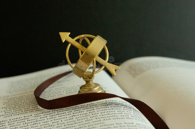 A miniature astrolabe figurine on pages of a book. stock image