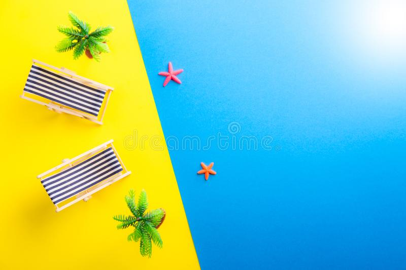 Miniature beach with deck chairs, palms and starfish on the colorful backgeound. Yellow and blue. Sand and ocean. Tropical resort royalty free stock photo