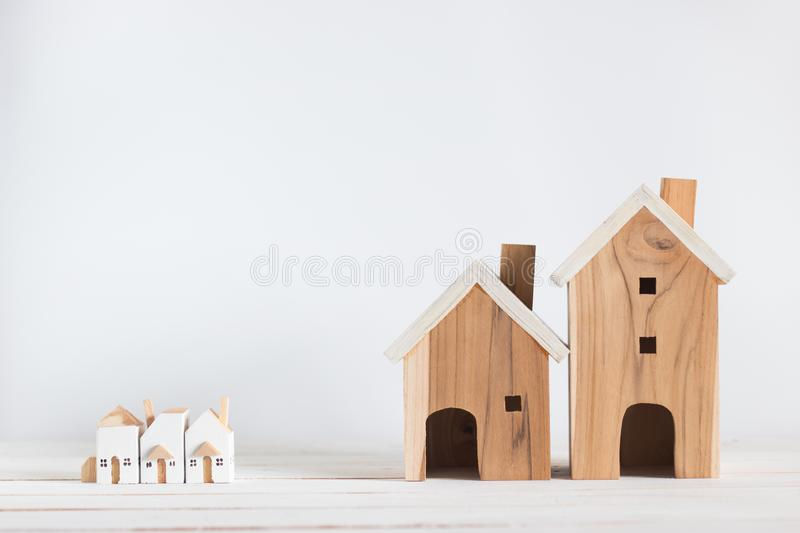 Miniature and big house model on white wood background. Copy space stock photo