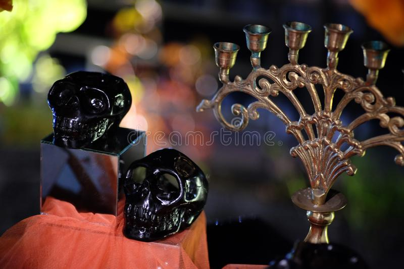 A miniature black human skull made of ceramic and a classic candle holder made of copper. stock photo