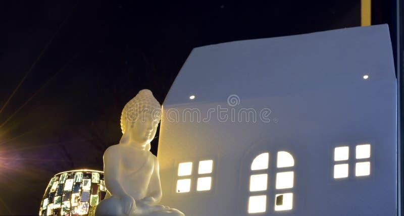 Miniature Buddha statue, sweet candlelight and white house stock photo