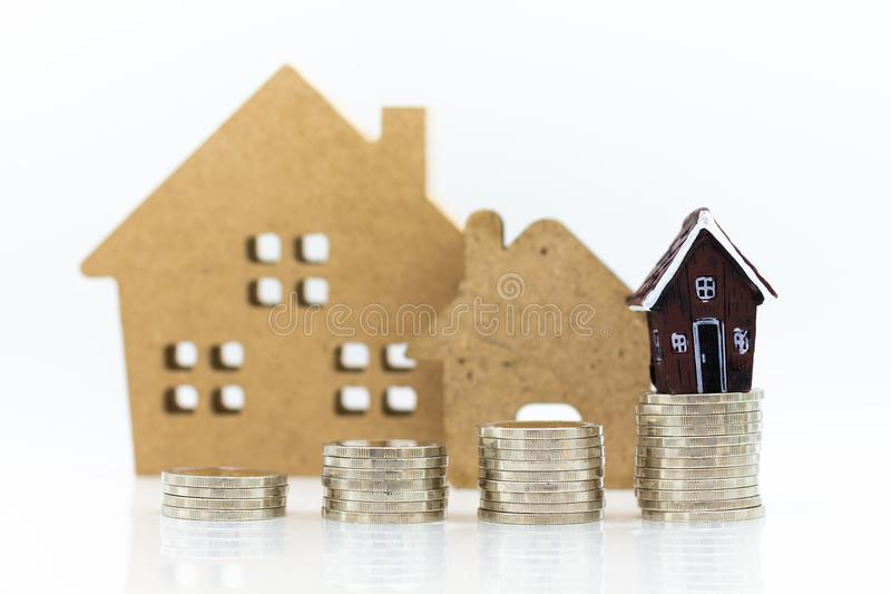 Miniature build: House resting with stack of coins. Image use mortgage and real estate investment.  stock photography