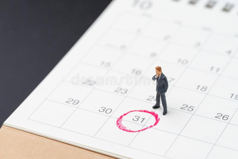 Miniature business man standing on desktop calendar with red circle on last day, 31 important resignation date, end of month, royalty free stock image