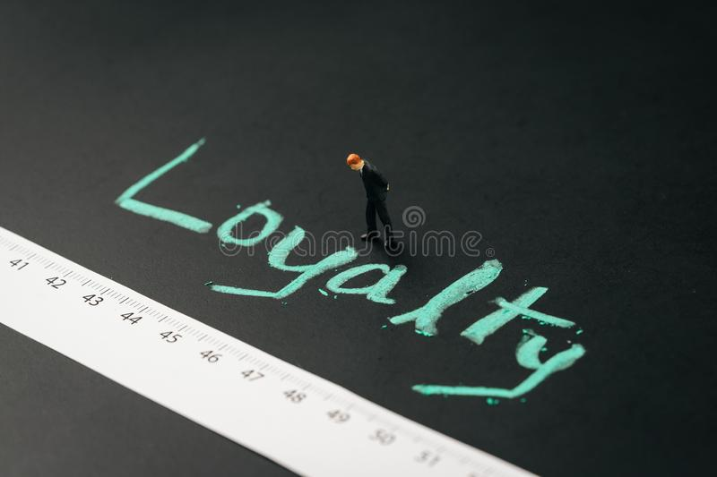 Miniature business man standing with measuring tape with handwriting chalk word Loyalty on blackboard, brand loyalty with royalty free stock images