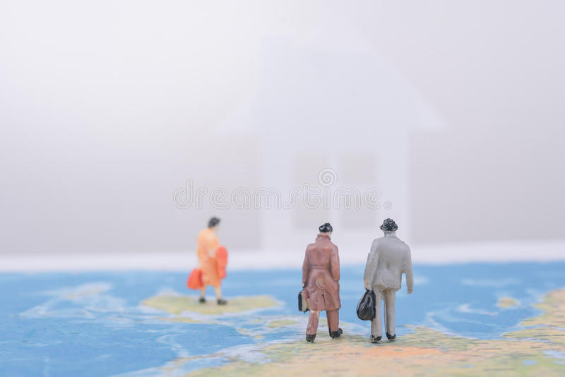 Miniature business people travel going home on world map. Business international travel concept royalty free stock image