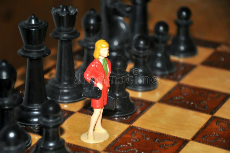Miniature business woman between chess pieces pawns figures on chessboard. Competition, gender, individuality concept stock photography