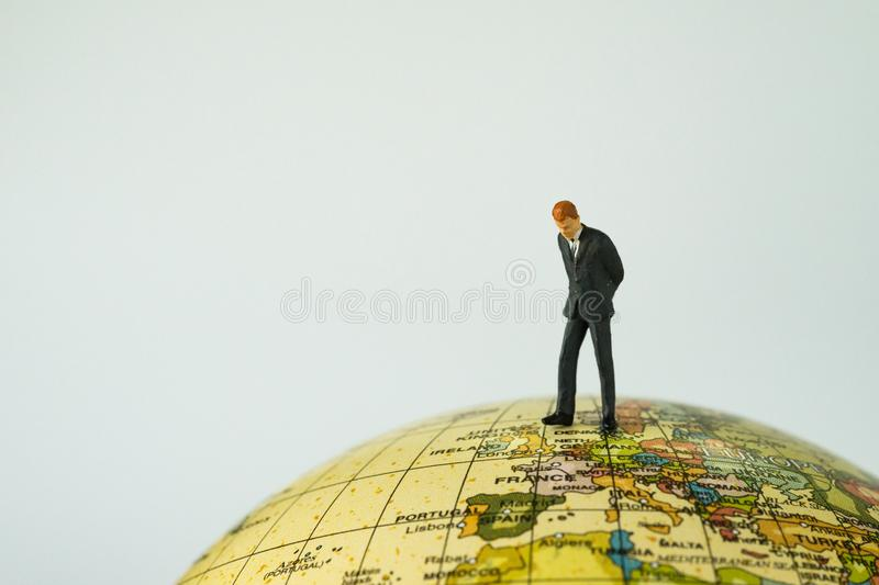 Miniature businessman leader standing and looking on Europe map. Globe as EU business economic or Brexit situation concept royalty free stock image