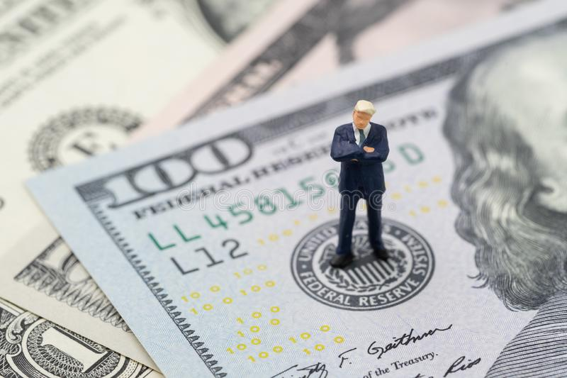 Miniature businessman leader standing and thinking on US Federal Reserve emblem on US dollars banknote as FED consider interest royalty free stock photo