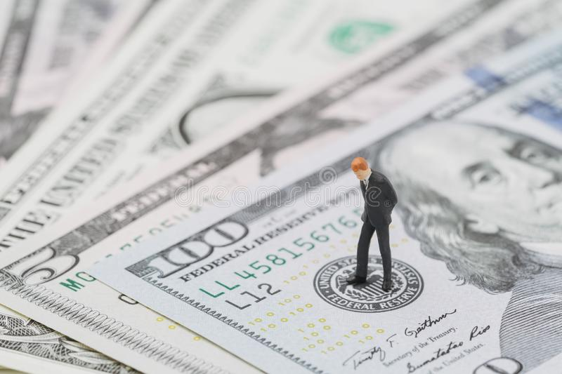 Miniature businessman leader standing and thinking on US Federal Reserve emblem on five dollars banknote as FED consider interest royalty free stock image