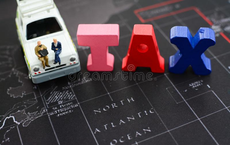 Tax refund, financial and business concept. Miniature businessman sitting and discussing on the car beside the wooden block TAX concept using as tax refund royalty free stock photo