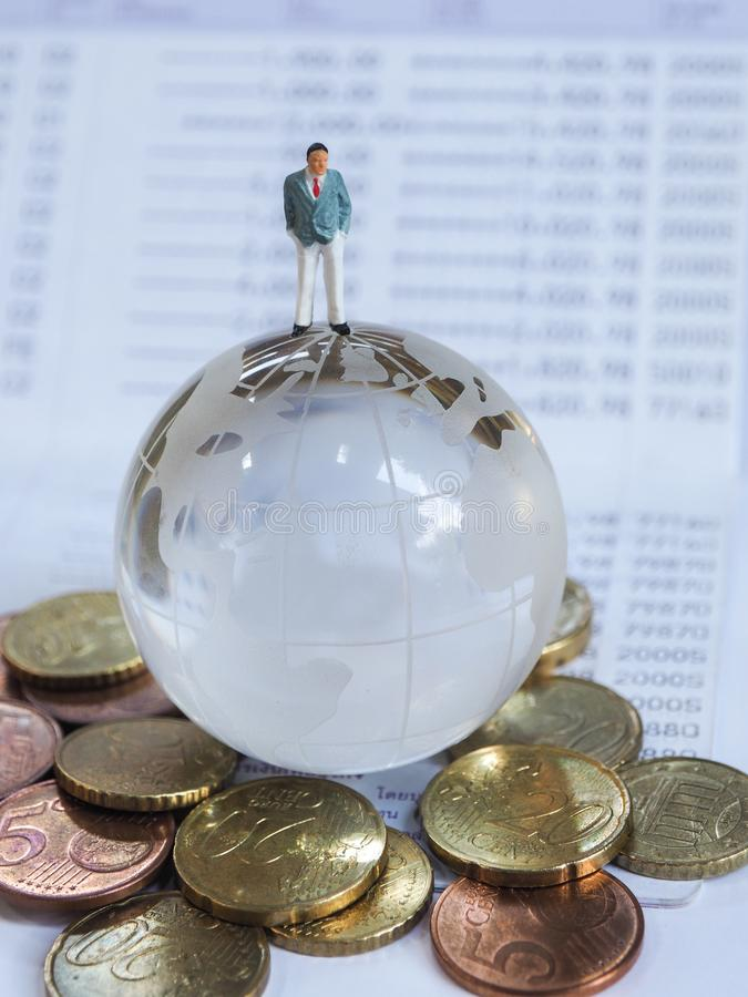 Miniature businessman stand on globe of glass, Euro coins and bo. Ok bank. Business and idea concept royalty free stock images