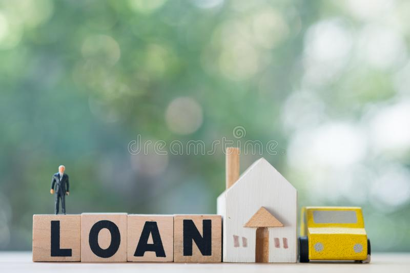 Miniature businessman stand on wood block words LOAN with wooden home and car royalty free stock images