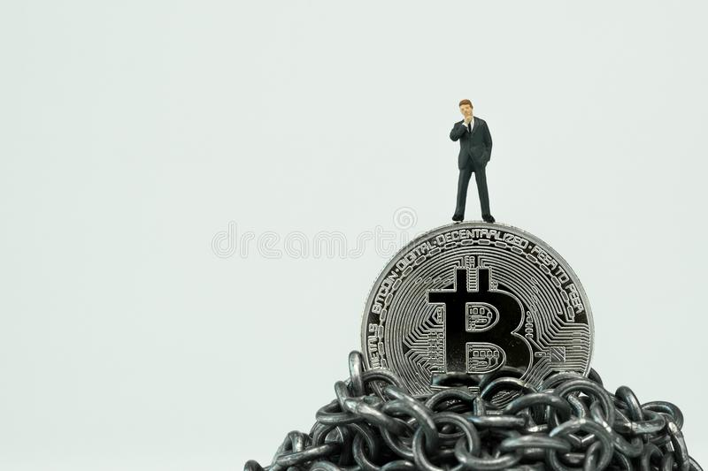Miniature businessman standing on Bitcoin on top of chain mountain thinking about high future value stock photo