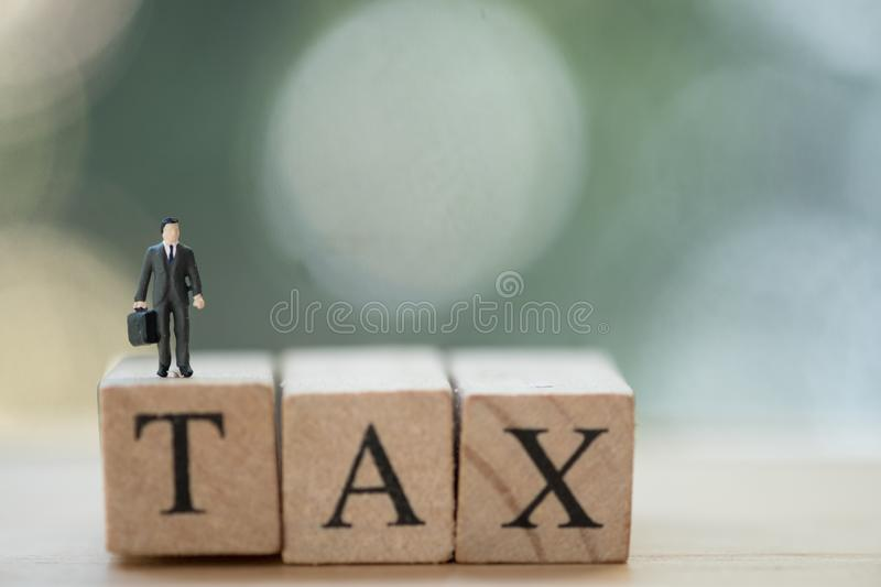 Miniature businessman standing on wood words TAX. Concept of pay annual income TAX stock images