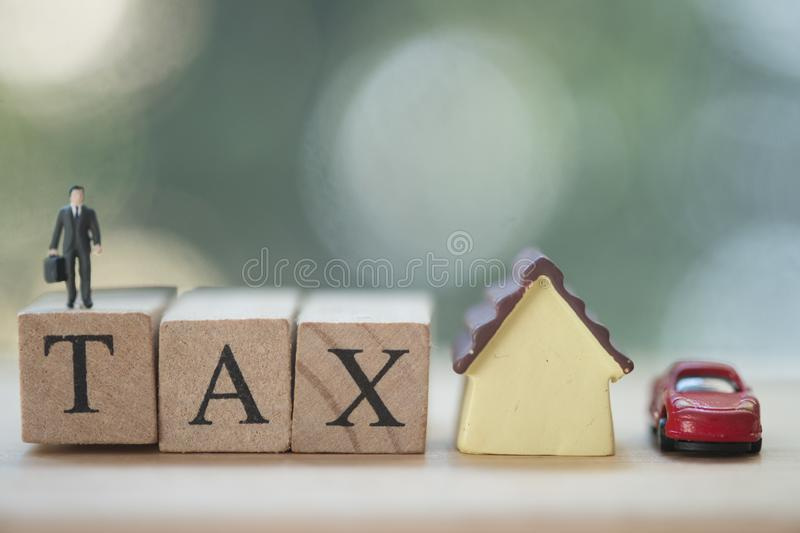 Miniature businessman standing on wood words TAX and miniature home and car. Concept of pay annual income TAX stock photos