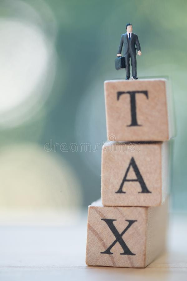 Miniature businessman standing on wood. Words TAX on top. Concept of pay annual income TAX royalty free stock image