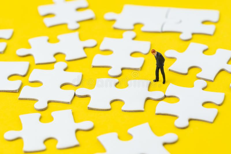 Miniature businessman in suit looking and thinking on white jigsaw puzzle on solid yellow background metaphor solution to solving. Business problem, creativity stock images