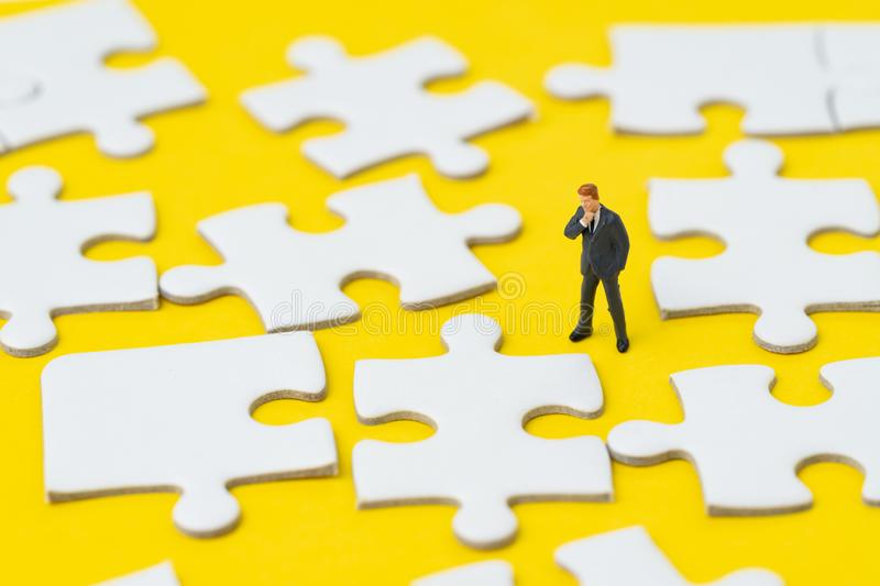 Miniature businessman in suit looking and thinking on white jigsaw puzzle on solid yellow background metaphor solution to solving. Business problem, creativity royalty free stock photography