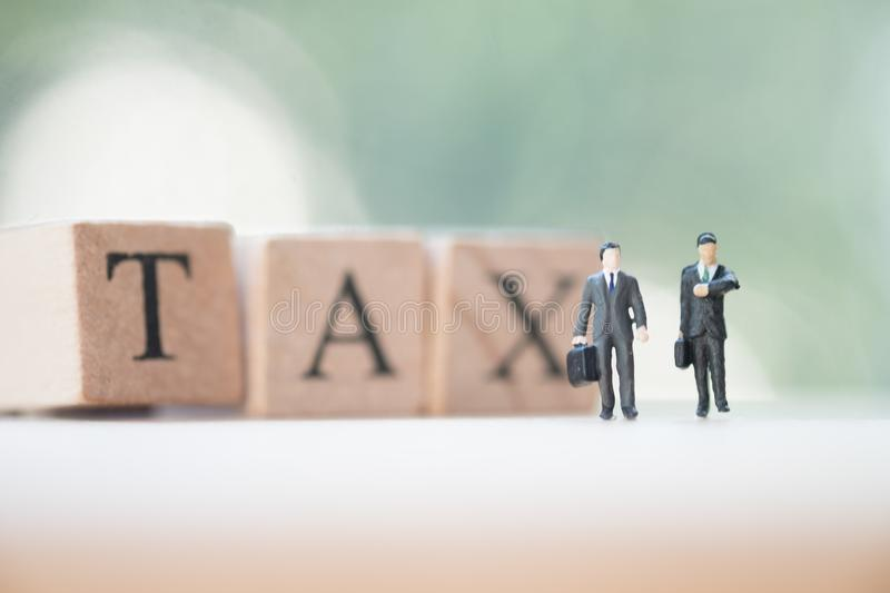 Miniature businessman with wood words TAX. Concept of pay annual income TAX royalty free stock photos