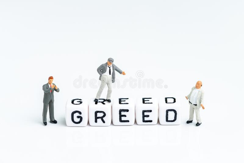 Miniature businessmen standing with cube block building the word Greed on clean white background using as greed and fear in stock. Market or money game and stock image
