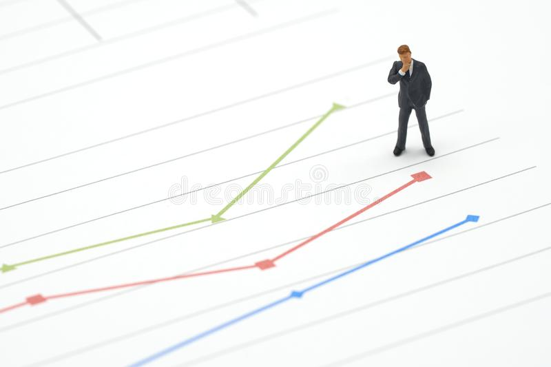 Miniature businessmen standing Investment Analysis on graph with performance as background strategy concept and Business concept w stock photos