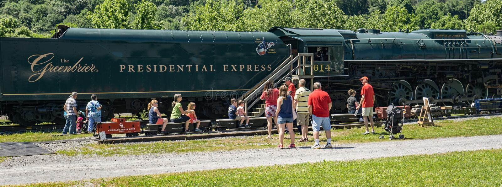 Miniature C&O Train Ride. Clifton Forge, VA – June 3rd: Children enjoying a miniature C&O train ride with the Presidential Express in the background at royalty free stock image
