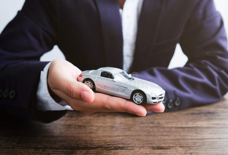 Miniature car model on hand, Auto dealership and rental concept stock images