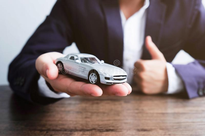 Miniature car model on hand, Auto dealership and rental concept royalty free stock image