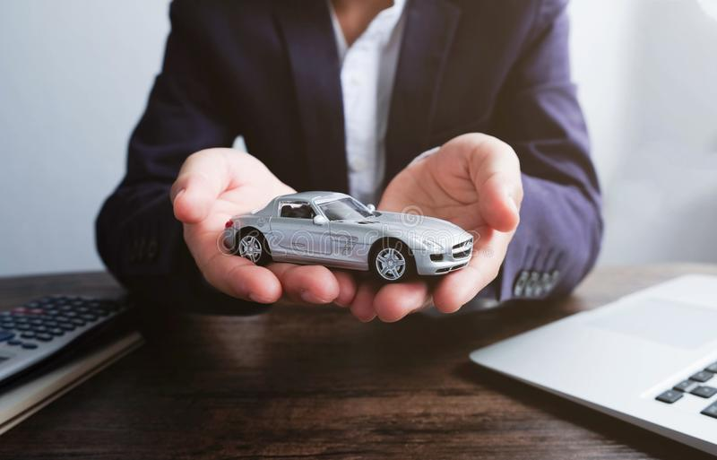 Miniature car model on hand, Auto dealership and rental concept. Car rental stock image