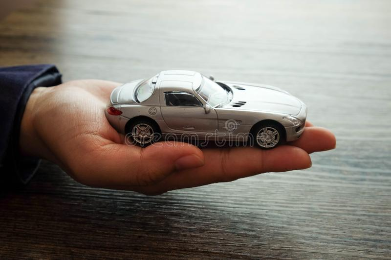 Miniature car model on hand, Auto dealership and rental concept. Holding car stock photo