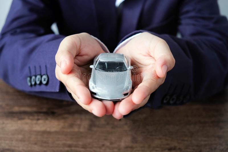 Miniature car model on hand, Auto dealership and rental concept royalty free stock photos