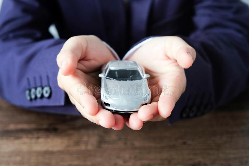 Miniature car model on hand, Auto dealership and rental concept. Transportation concept stock image