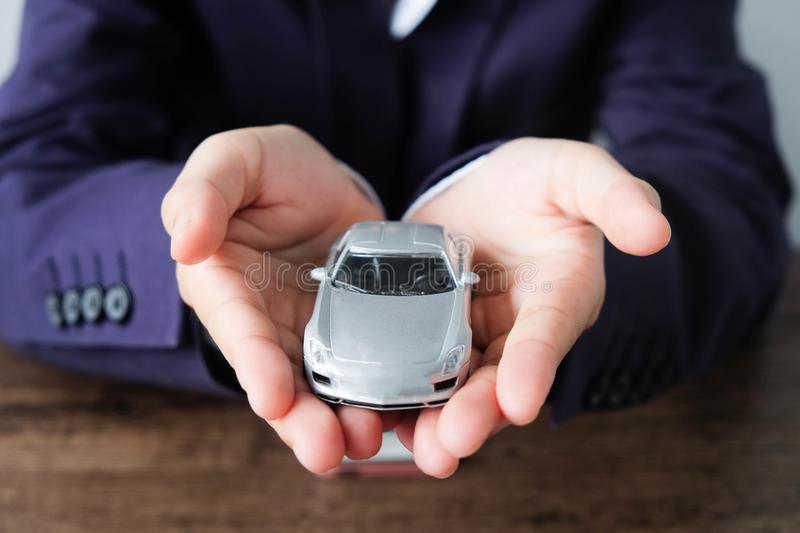 Miniature car model on hand, Auto dealership and rental concept. Transportation concept stock photo